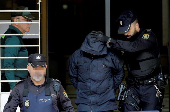 El detenido Jorge Ignacio P. a su salida de los juzgados de Alzira conducido por la Policía Nacional. EFE/ Manuel Bruque