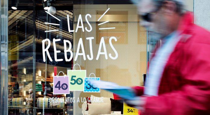Un hombre pasa ante el escaparate de una tienda que ofrece rebajas de hasta el 50%. EFE/Manuel Bruque