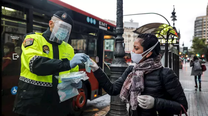 Un policía local entrega una mascarilla a una mujer en el centro de Valencia. / FOTO: Rober Solsona - Europa Press.