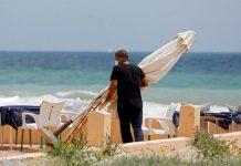 Un empleado de un restaurante protegido con mascarilla en la playa de El Saler. / FOTO: Kai Försterling (EFE).