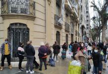 Centenares de personas hacen cola en el reparto de alimentos de la calle Colón.